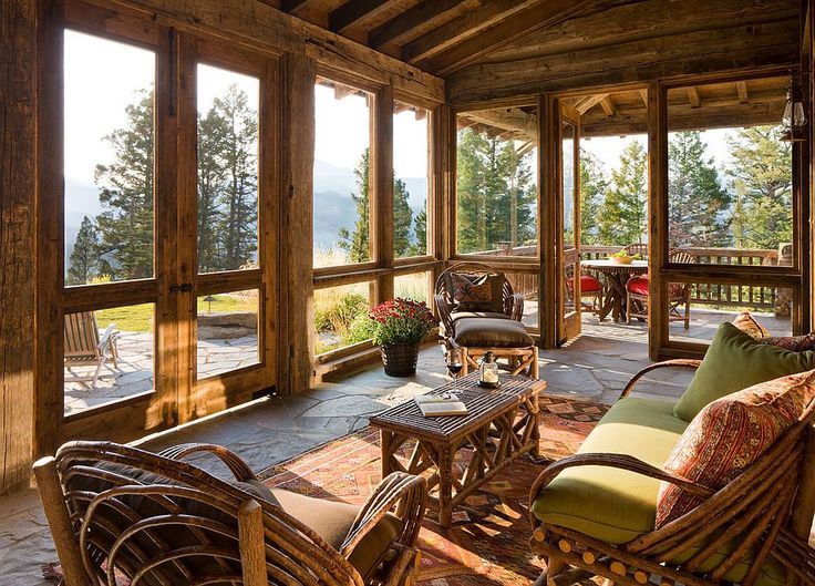 Rustic cabin sunroom that flows into the deck acts as a bridge between the interior and the outdoors [Design: Miller Architects LTD]