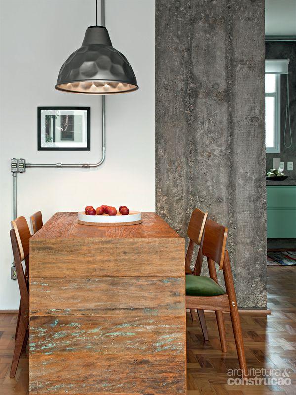 """O pendente da sala de jantar é feito à mão por Brunno Jahara e carrega a grande marca do designer: o aspecto """"batido""""."""