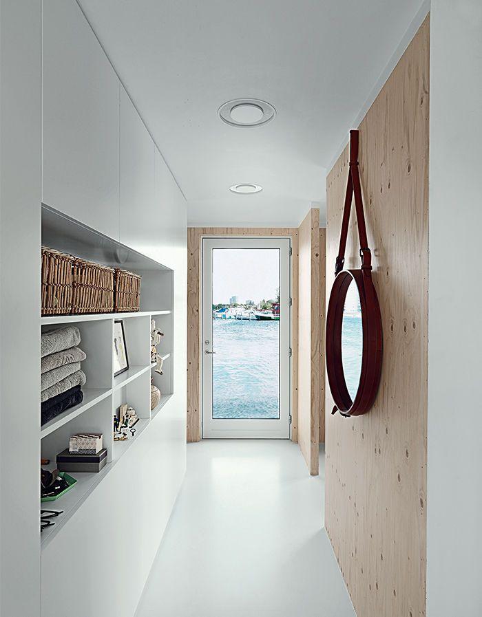 コペンハーゲン湾に浮かぶ細長いフローティング住宅のリビング・ダイニング・キッチンとベッドルームの間の廊下 構造用合板