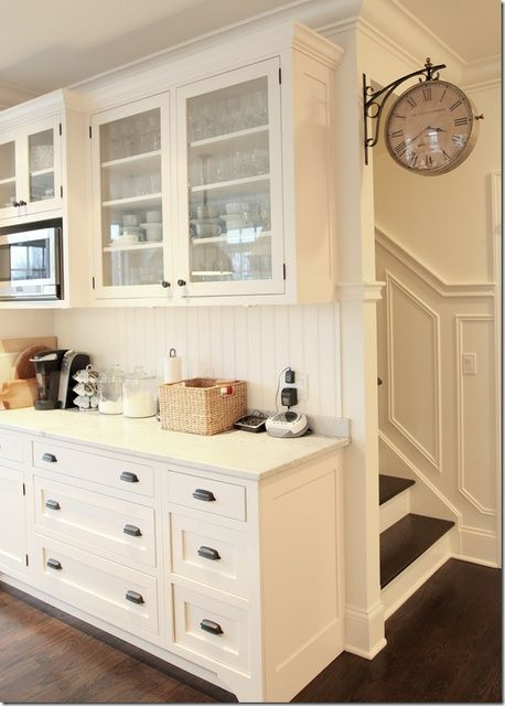 A classic white kitchen. Love the glass cabinets and the clock. It is all great!!  :)