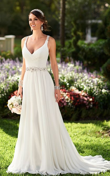 Classic and ethereal, this chiffon Grecian-style  wedding gown from the Stella York collection takes beachside romance to the next level. Featuring fine Diamante detailing along the shoulder straps, waist, and head-turning keyhole back, this gown will set a new standard for seaside nuptials, The fitted bodice boasts soft ruching and the back zips up beneath sparkling crystal buttons to complete your effortless look.