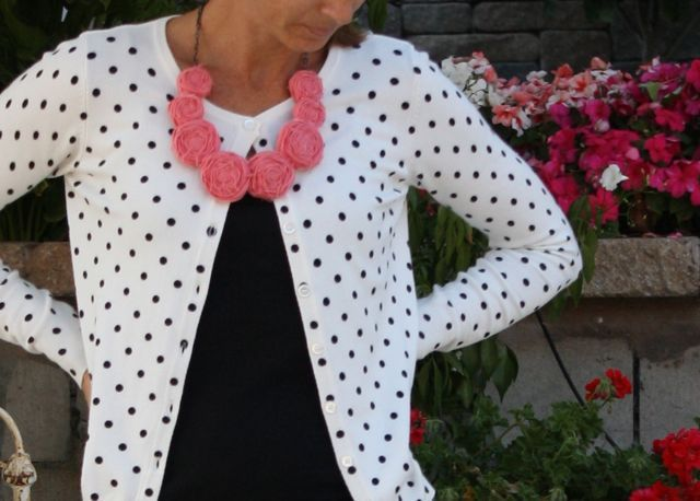 White and black polka dot cardigan with bright statement necklace.