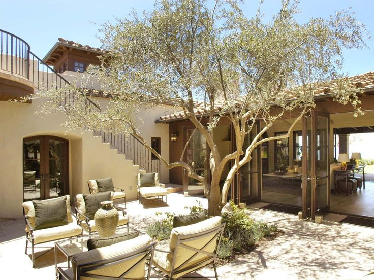 This mission style home promotes and open transition between the indoors and outdoors with gaping french doors. A seating area within the courtyard is ready for entertaining, and an exterior stairway leads to a deck overlooking the courtyard.