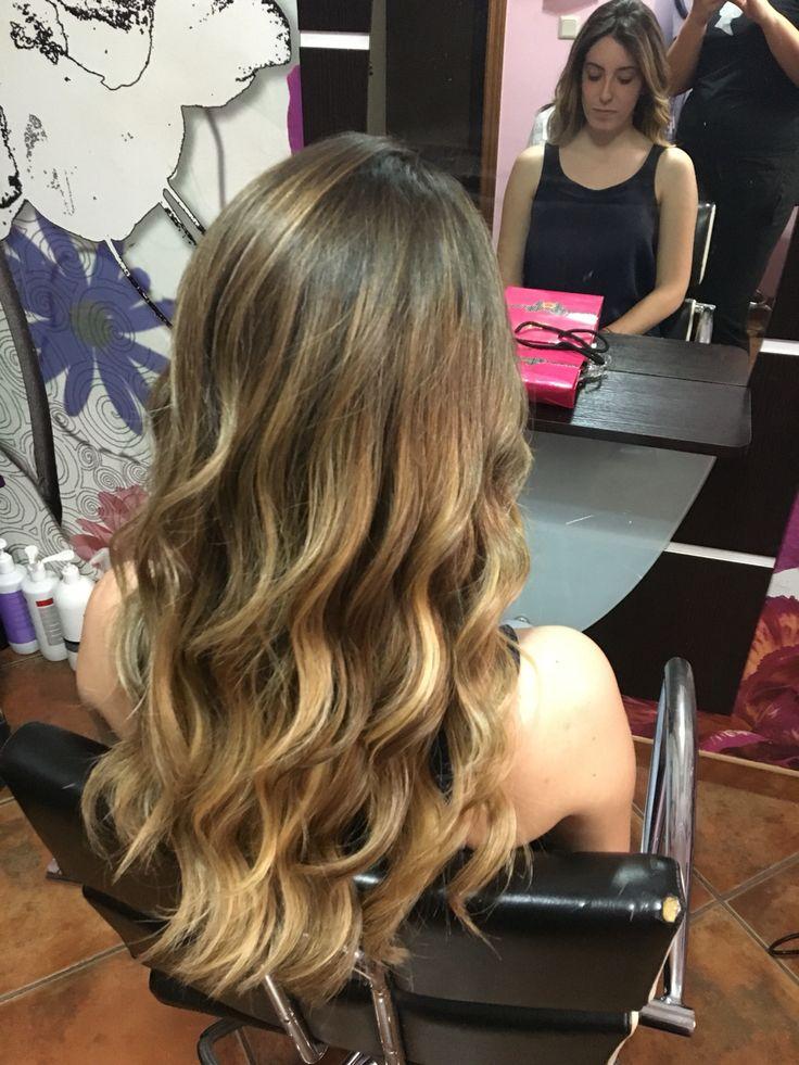 Mechas ombre en cabello rubio oscuro. Degradado de color perfecto. Peinado con ondas surferas
