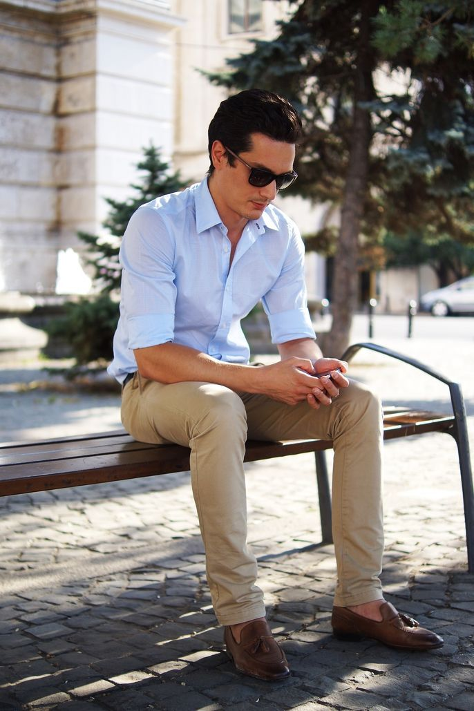 Shop this look on Lookastic:  https://lookastic.com/men/looks/light-blue-long-sleeve-shirt-khaki-chinos-brown-tassel-loafers-dark-brown-sunglasses/5666  — Brown Leather Tassel Loafers  — Khaki Chinos  — Light Blue Long Sleeve Shirt  — Dark Brown Sunglasses