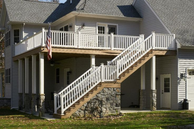 A two story deck on a custom home, with outdoor stairs.