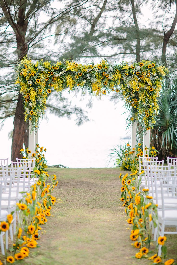 Yellow wedding ceremony (backdrop and aisle) decor with sunflowers //Gary and Yanny's bright, sunflower-filled destination wedding in Phuket, Thailand