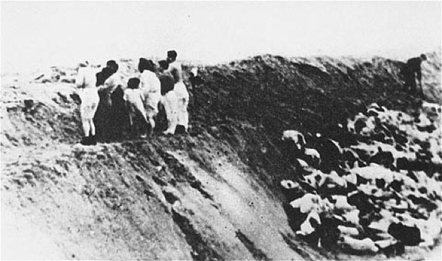 "The same group, lined up at the ditch next to a pennant marking the place where they were to stand. Ruben-Aron Grinfeld is second or third from the right, next to his mother and sisters. Little Cilla is holding her mother's hand. A ""kicker"" is visible on the extreme right, pushing bodies into the ditch that were stuck on the ledge."
