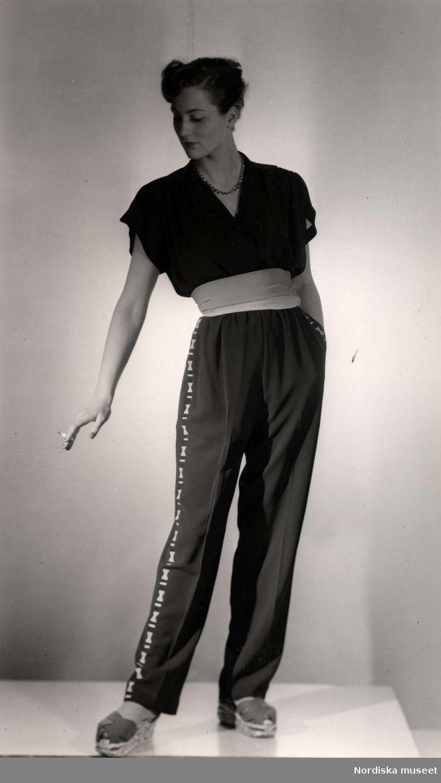 California - sommarkläder visas av kvinnlig modell på varuhuset Nordiska Kompaniet i Stockholm 1947. Mannekängen poserar iklädd en kortärmad, ledig overall med brett textilskärp. På fötterna espadriller med flätad ovandel. I handen håller hon en cigarett.
