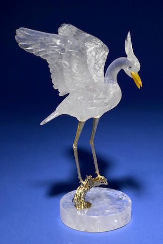 Rock Crystal Carving of a Stork By Peter Mueller Brazil  Utilizing highly transparent, fine quality rock crystal quartz, the beak carved of yellow agate, this rendering of a stork with outstretched wings, evokes a vision of the bird on a lake. The gold vermeil legs are removable from the gold vermeil branch upon which it rests, which emerges from the circular rock crystal base.