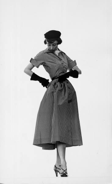 Model Dorian Leigh wearing pin-point taffeta dress w. full skirt by Mollie Parnis, long black gloves.  Location:New York, NY, US  Date taken:1950  Photographer:Gjon Mili
