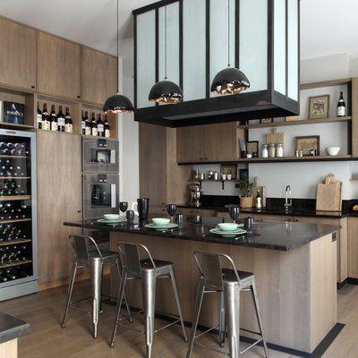 La cuisine conçue par David Gaillard exploite toute la hauteur sous plafond. Elle est conçue autour d'un îlot central qui accueille les plaques de cuisson. Le plan de travail offre un large débordement qui sert de coin repas. Tabourets de bar, Tolix.