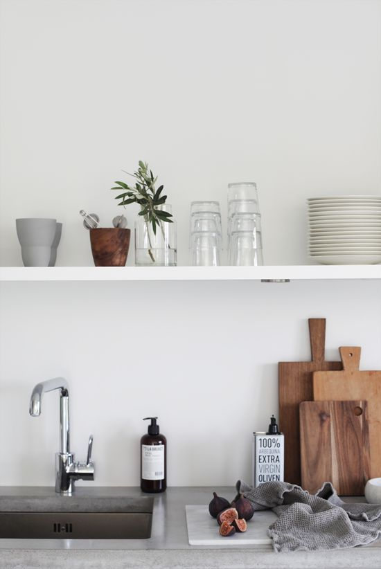 Minimalist shelving, glass, pottery, cutting boards, and a plant. A lovely, airy kitchen.