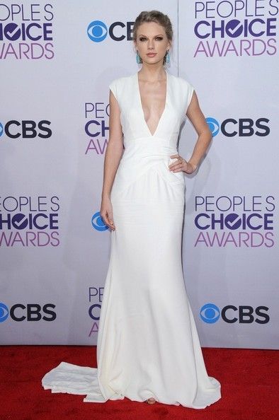 Taylor Swift Evening Dress - Taylor Swift has never looked so regal! Check out this dramatic white gown she wore to the People's Choice Awards.  She looks ready to walk down the aisle, no?   Brand:  Ralph Lauren