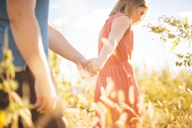 A beautiful couple walking hand in hand together in tall grass with the sun setting and shining through at Happy Apple Farms in Penrose, Colorado | Couples Photography