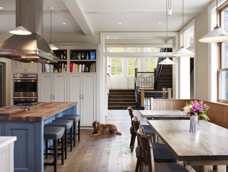 Pendants illuminate the kitchen, which includes custom cabinetry and a built-in banquette both designed by Quinn. The island's wood butcher-block countertop is from John Boos & Co. and counter stools are from Hickory Chair. Fredman Design Group conceived the Woodland Furniture tables, which coordinate with Bausman & Company chairs.