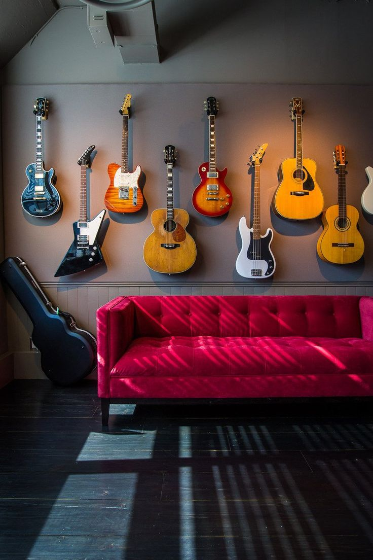 Great music room design. Love that couch and all the guitars against the grey wall.