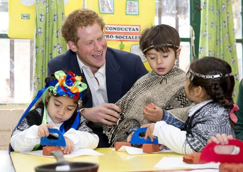 Prince Harry takes part in the kids games as he visits kindergarten of indigenous children a on June 27, 2014.