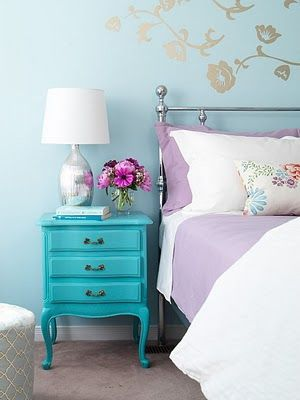 Everything here is lovely:  the silver painted wall flowers, the mercury glass lamp, the nightstand color against the lavender bedding, the silver bed...