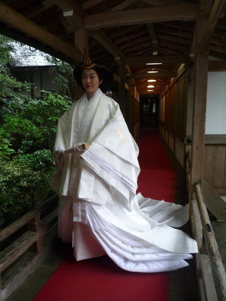 A woman wearing an all white junihitoe for a wedding. White was worn in the first several weeks of a child's birth during the heian era. Now white is an option for weddings.