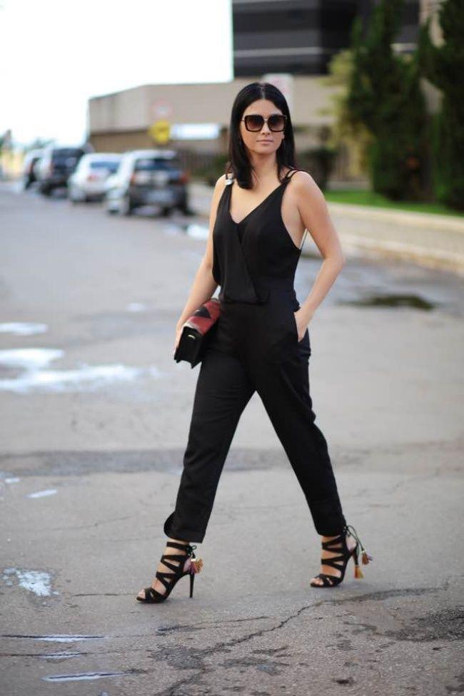 Macacão pantacourt preto com sandália de tiras e detalhe colorido, além de uma bolsa com desenhos geométricos.