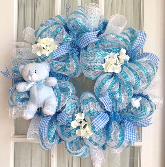 Display your joy of your new arrival with this precious handmade deco mesh baby boy wreath in blue and white with teddy bear. Great baby