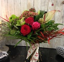 A hand tied flower bouquet featuring red and pink roses with a seasonal selection of other flowers, foliages and added Christmas sparkle.