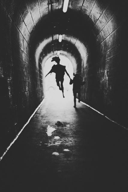 Girl jumping with backlight in tunnel