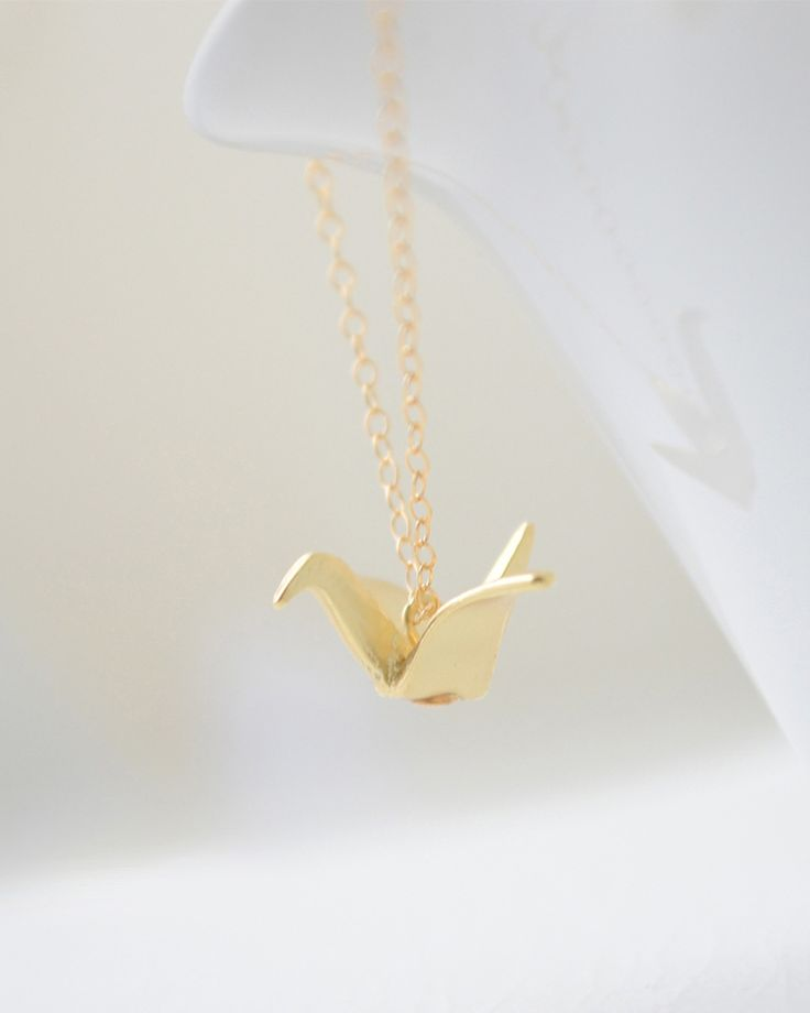 Simple gold origami crane on shiny, petite gold necklace