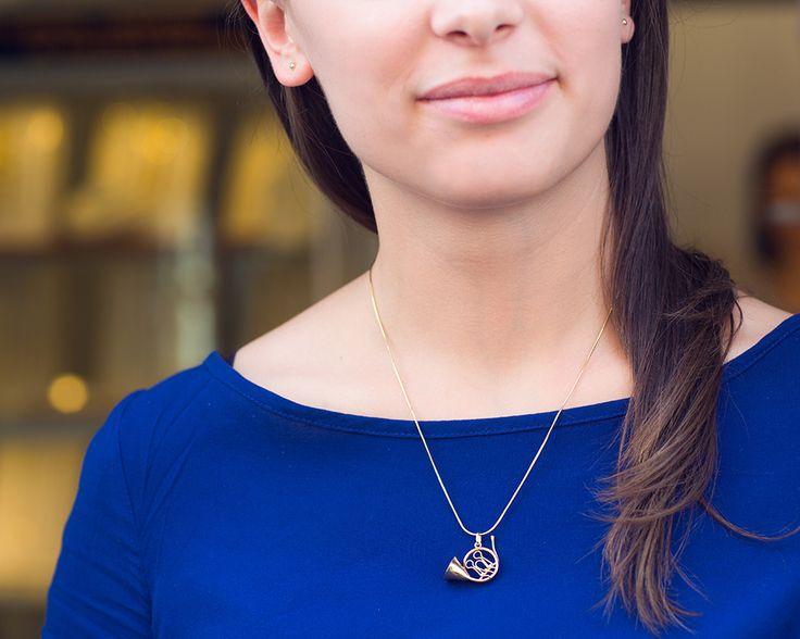 Złota zawieszka w kształcie trąbki dobrze komponuje się z niebieska sukienką?