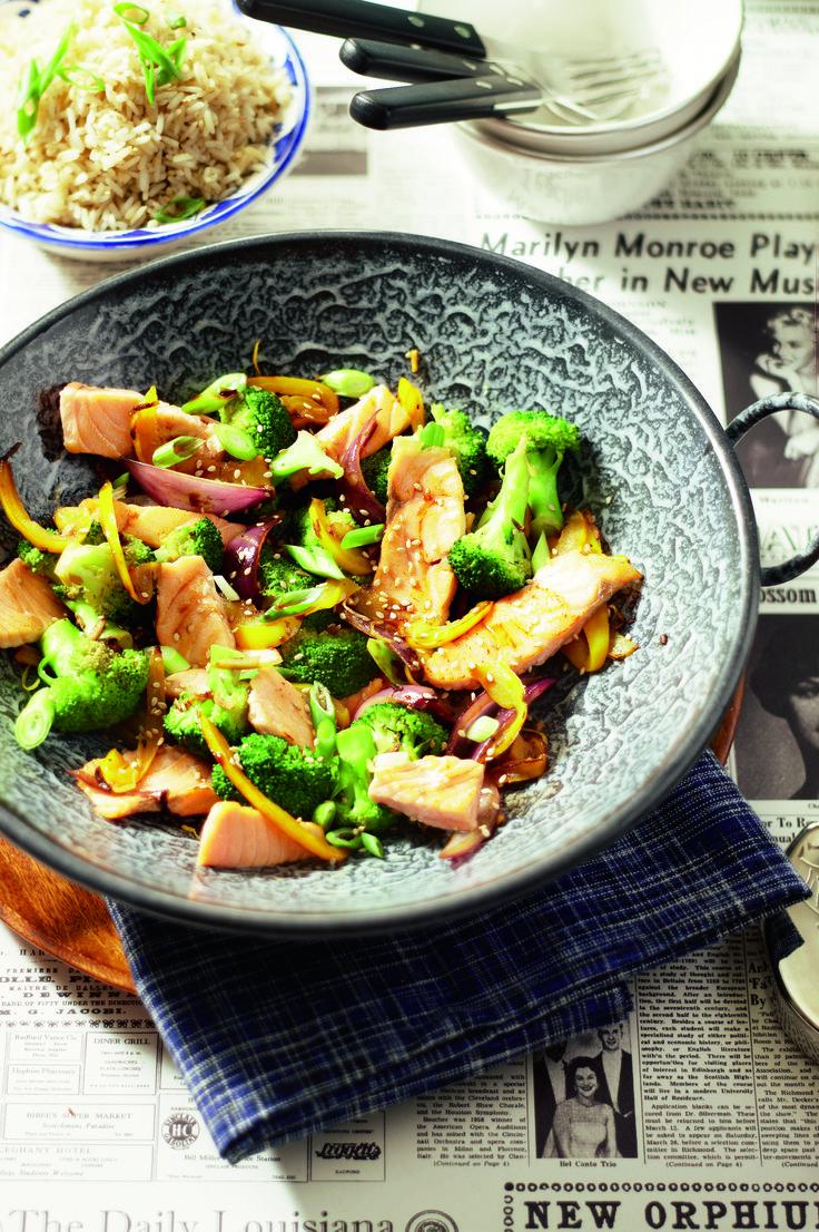 Verhit 1 eetlepel olie en roerbak hierin de visrepen met citroenrasp 2-3 minuten op een hoge stand. Bestrooi de zalm met zout en peper, schep de vis uit de pan en houd hem warm onder aluminiumfolie. Verhit de rest van de olie en roerbak hierin de gember, knoflook, ui en paprika 3-4 minuten. Schep de broccoliroosjes erdoor en bak nog 2 minuten. Voeg de vis, het citroensap en de sojasaus toe en verwarm even. Serveer het gerecht bestrooid met sesamzaad (eventueel geroosterd in een droge hete…