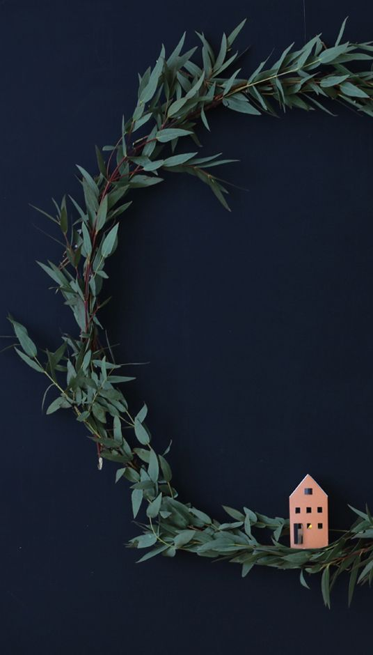 Eucalyptus wreath holding a tiny christmas paper house with led light... HEIM houses, 12 easy DIY pre-cut and prefolded in one set (price € 15.95)