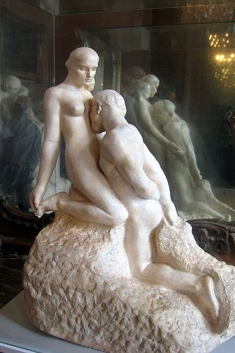 L'Eternelle Idole -1889- embodies typical Auguste Rodin themes -strength-sensuality-gentleness & in particular, relationship between male & female. It displays Rodin's reverence for the female body, with a restrained male, arms behind his back, knelt before the woman kissing her tenderly below her left breast, just over her heart. Suggestion was made that this image may be a continuation of Rodin's The Kiss. It has been documented to have been influenced by Camille Claudel's Sakountala
