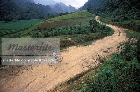 A young girl rides her bike on a dirt road near Bac Ha, Vietnam.