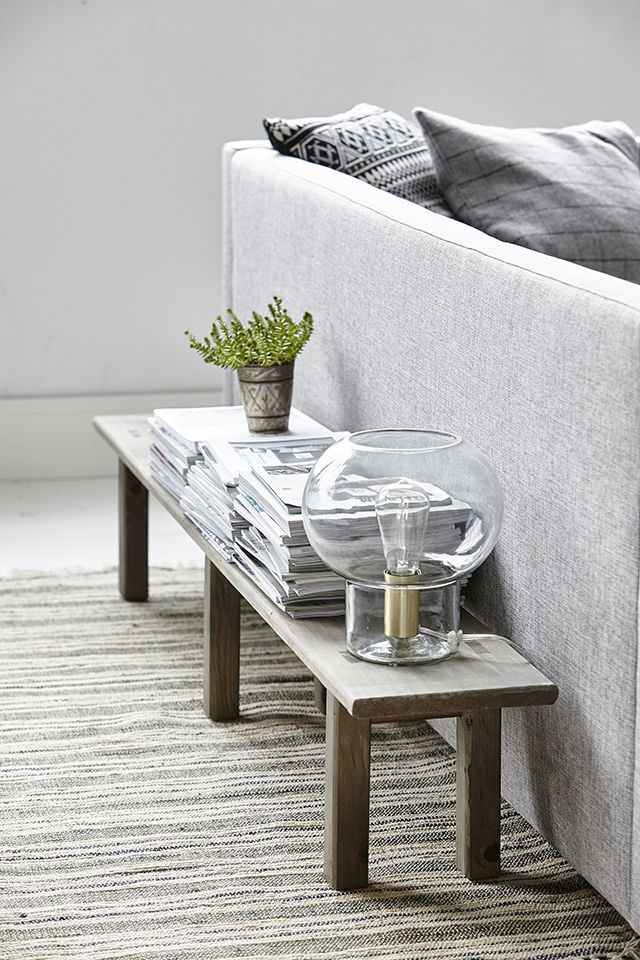 Bench Seat Styling, small plant, magazines, sheer side lamp, grey sofa and grey walls