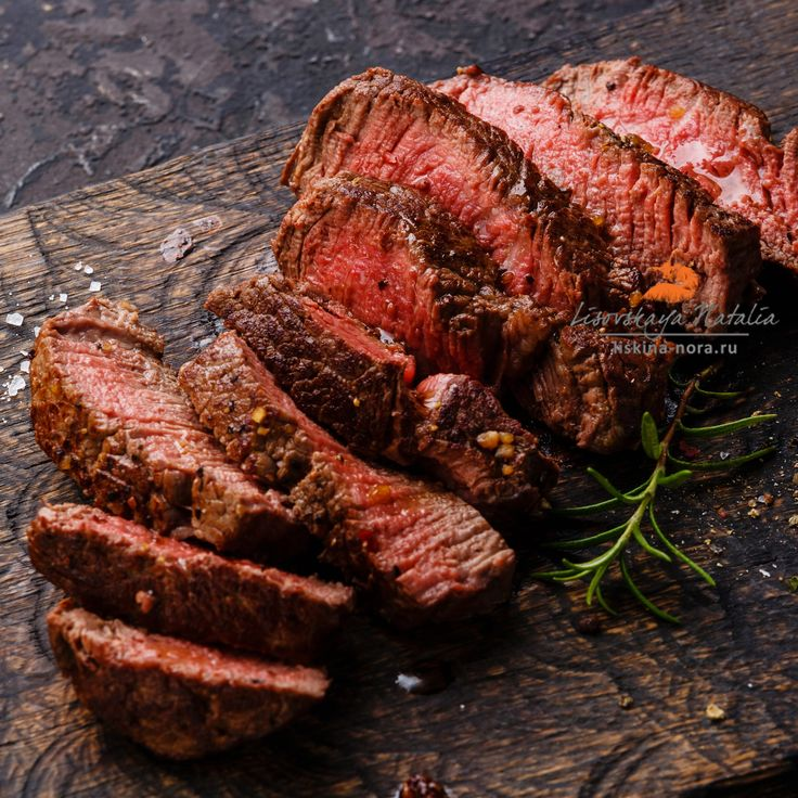 Sliced grilled steak roastbeef and rosemary on wooden cutting board