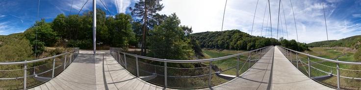 """Dieses Panorama zeigt die 124m lange Hängebrücke """"Victor-Neels-Brücke"""" in der Nähe von Vogelsang im Nationalpark Eifel. Das Panorama wurde, im Gegensatz zum Panorama von der Mitte der Brücke http://www.360cities.net/image/national-park-eifel-vogelsang-victor-neels-bridge-germany, von der Pylonenseite aus erstellt. Weitere Informationen finden Sie unter http://www.baukunst-nrw.de und http://www.ib-cornelissen.de/bruecken/48.htm"""