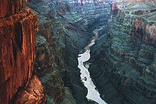 Grand Canyon National Park, Arizona. The centerpiece of the park is the Grand Canyon, a gorge of the Colorado River. The Grand Canyon is 277 miles (446 km) long, up to 18 miles (29 km) wide and attains a depth of over a mile (6,000 feet or 1,800 metres). Nearly two billion years of the Earth's geological history have been exposed as the Colorado River and its tributaries cut their channels through layer after layer of rock while the Colorado Plateau was uplifted.