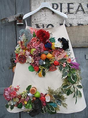Skirt 246 by Alison Willoughby is a collection of fake and plastic food, feathers, fake flowers and shrubs applied to a canvas skirt base.