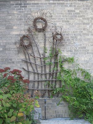 Love the daisy-looking flower wreaths on this twig trellis - so easy and so cute!