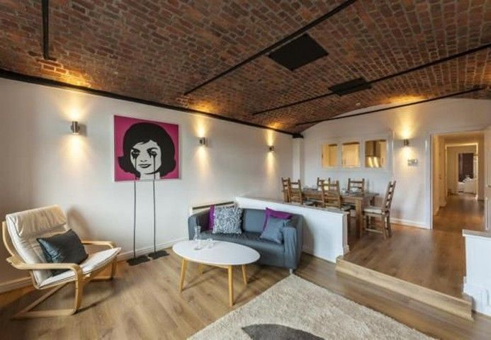 Exposed brick ceilings and original features in modern converted warehouse apartment on Waterloo Road, Liverpool.