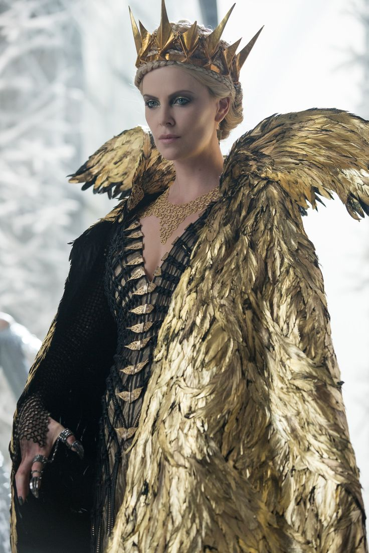 """Charlize Theron as the evil Queen Ravenna from """"The Huntsman: Winter's War"""" (2016). Costume design by Colleen Atwood. Atwood chose to expand upon Ravenna's relationship with the Magic Mirror by incorporating luminous gold into Theron's costumes while bringing back the character's iconic crown and raven feathered cape."""