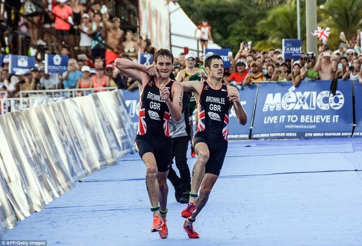 British athlete Alistair Brownlee (left) helps his brother Jonathan Brownlee (right) befor...