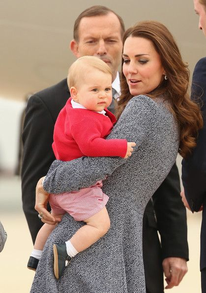 Australian Prime Minister Tony Abbott looks on as Catherine, Duchess of Cambridge holds Prince George of Cambridge as they leave Fairbairne Airbase to head back to the UK after finishing their Royal Visit to Australia on April 25 2014 in Canberra, Australia