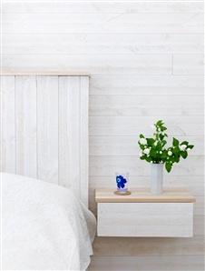 Mesita de noche - Sovrummet är inrett med vitmålad råspont.