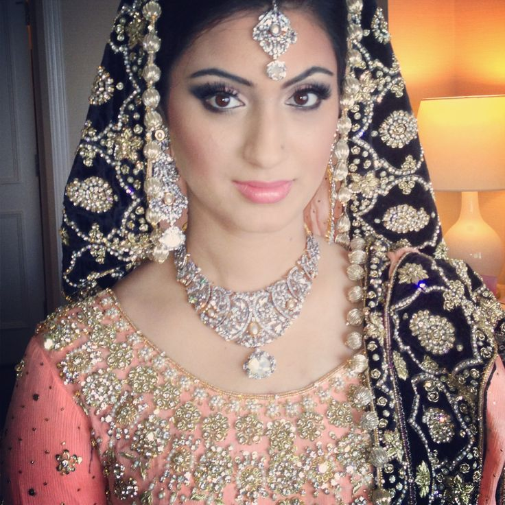 Love the pink and dark blue color of her desi bridal dress. The gold rounds framing the veil add the perfect bridal touch.