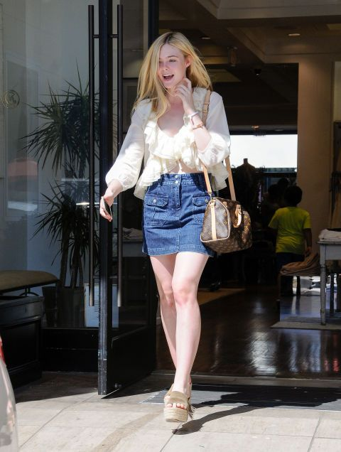Elle Fanning out in L.A. wearing a denim mini and carrying a Louis Vuitton bag. See all of the actress's best looks.