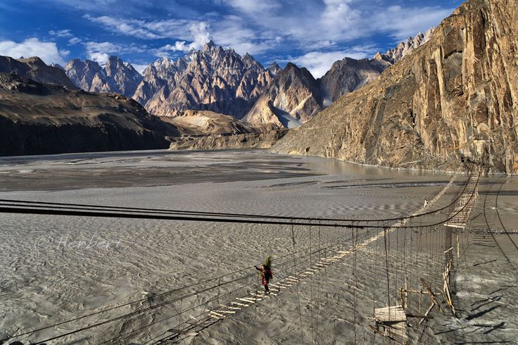 The Hussaini Bridge over the rapidly flowing Hunza River with cathedral mountains in the background, connecting Upper Hunza/Baltistan with the Karakorum Highway, Pakistan.