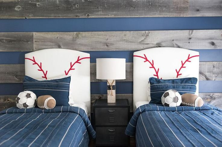 Blue and gray boys' bedroom features blue walls lined with gray wood planks lined with a pair of white and red baseball themed headboards on twin beds dressed in blue bedding as well as soccer ball and football pillows flanking a shared metal industrial nightstand.