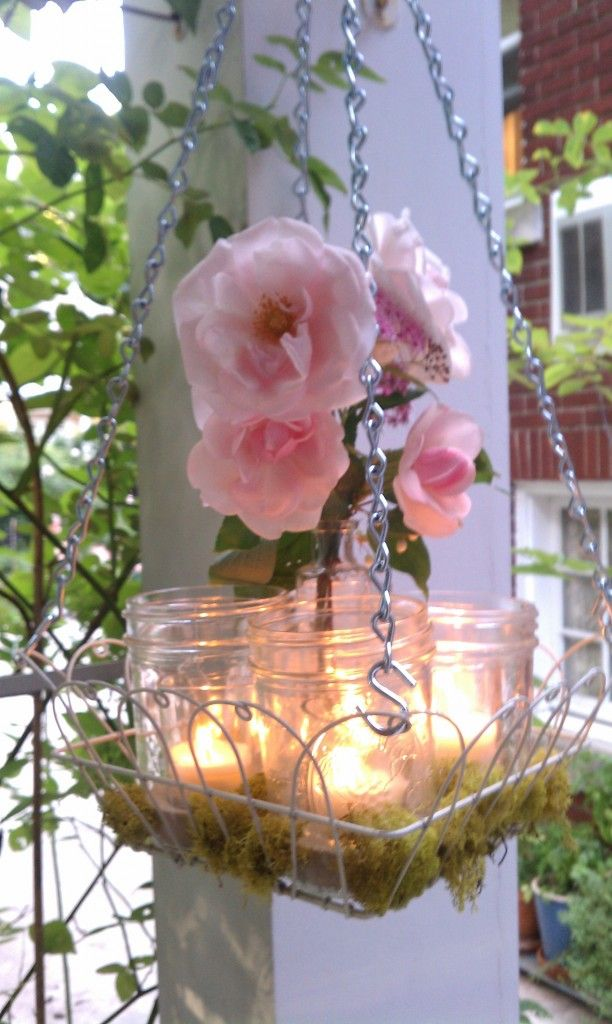 Simple Outdoor Chandelier...Find any wire basket that will hold jars, glass votives, or even simple drinking glasses.  Fill them with sand or gravel and a votive.  Squeeze a small bunch of flowers in the center and place moss around the bottom of the glass containers.  Just make sure your flowers are high enough from the flames so you don't start a fire!  Using small S hooks and chain, suspend the basket where ever you like…simply lovely.